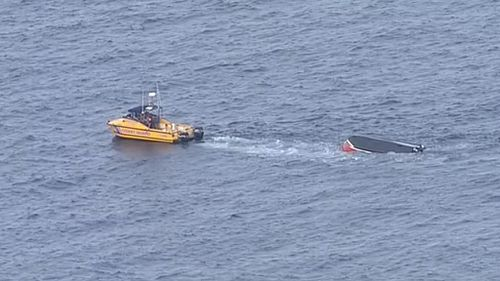 The Coast Guard approaches the overturned boat. (9NEWS)