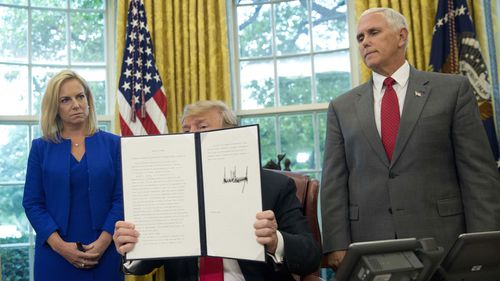 President Donald Trump shows off his executive order with Homeland Security Secretary Kristjen Nielsen and Vice President Mike Pence. (AAP)
