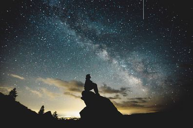 Person sitting on a rock looking at the stars.