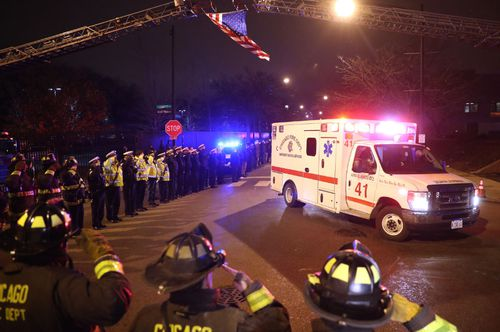 Firefighters and police salute the ambulance carrying the body of shooting victim Officer Samuel Jimenez.