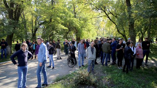 Local people gather near a school where a bomb is believed to have been detonated in Crimea, Russia.