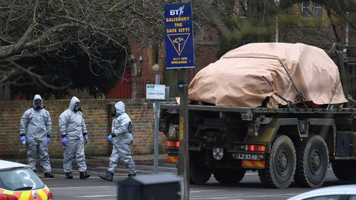 Military in protective clothing prepare to remove vehicles from a car park in Salisbury. (AAP)