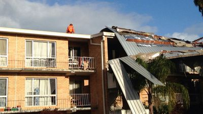 An SES worker examines the damage after the roof of an apartment in Attadale blew off in last night's wild weather. (9NEWS)