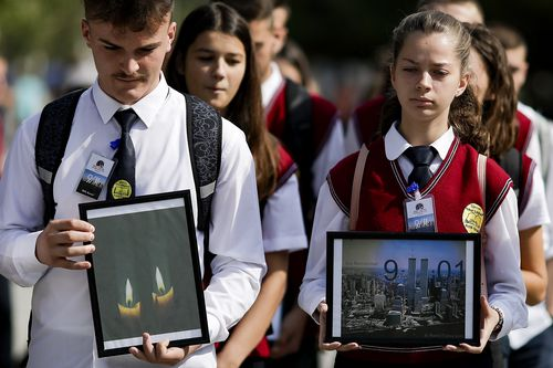 Kosovo Albanian students hold pictures of World Trade Center's twin towers while marching in the capital Pristina, Kosovo,