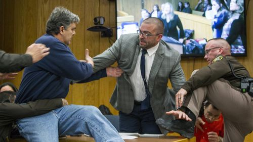 Randall Margraves, father of three victims of Larry Nassar, lunges at the serial child molester. (AAP)