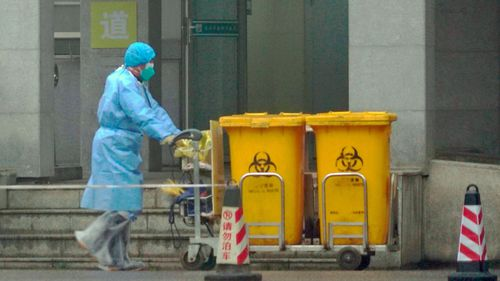 Staff move bio-waste containers past the entrance of the Wuhan Medical Treatment Center, where some infected with a new virus are being treated.