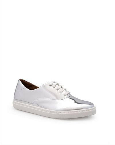 "These playful, high-shine sneakers offer a flashy finish to any workday outfit. Match them back with a classic LBD and relaxed blazer or pair them with simple monochrome separates for corporate cool.  <br> <br> Country Road Riley sneaker, $129. <a href=""https://www.countryroad.com.au/shop/woman/shoes/sneakers/60196027-901/Riley-Sneaker.html"" target=""_blank"">Countryroad.com.au</a><br>"