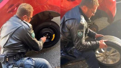 Cop helps change flat tyre