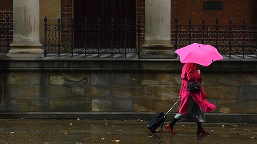 Widespread rain and thunderstorms are predicted for parts of Australia for the next four days.A woman wearing a pink coat and carrying a pink umbrella walks through the rain past St James Church in the Sydney CBD, NSW. 17th March, 2021. Photo: Kate Geraghty