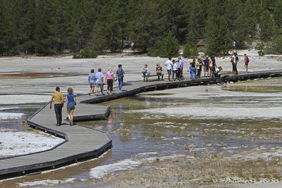 Visitors walk on the boardwalk in the Norris Geyser Basin in Yellowstone National Park, Wyoming,