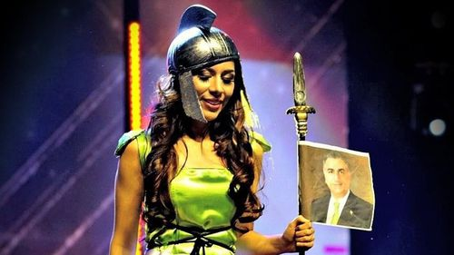Bahari pictured using an image of Pahlavi and the flag of the former Iranian monarchy as props during a recent competition.