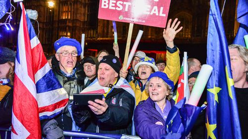 Remain supporters take in the news outside the Houses of Parliament.