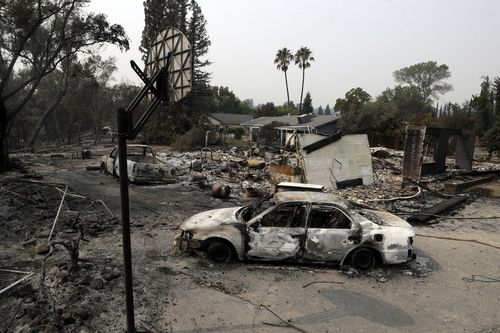 Burned vehicles sit in front of a wildfire-ravaged home, Sunday, July 29, 2018, in Redding, Calif. Picture: AAP