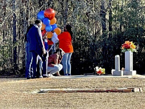 Wanda Cooper-Jones kneels before the grave of her son, Ahmaud Arbery, at the New Springfield Baptist Church in Waynesboro, Ga.