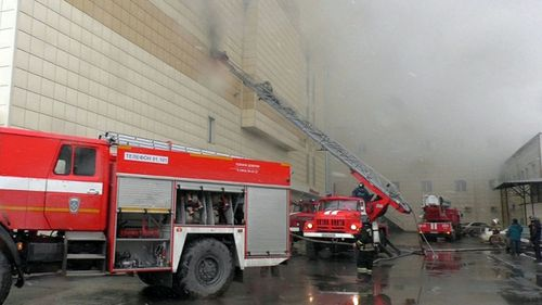Fire fighters climbing up onto a top floor of a shopping mall Zimnyaya Vishnya on fire in the Siberian city of Kemerovo, Russia.