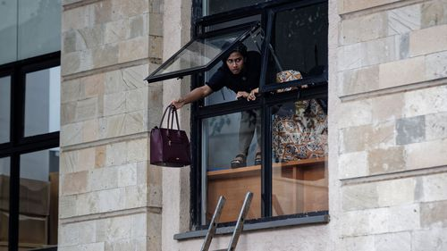 A woman throws her handbag out of the window of a luxury hotel as she flees the hotel complex.