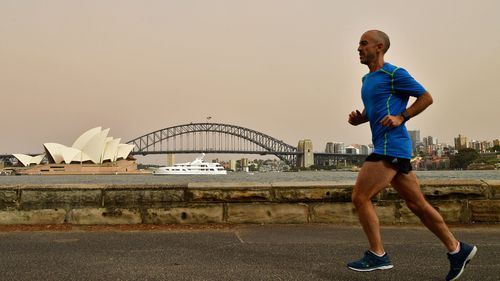 A man runs by the harbourside a day after strong winds blew the cloud in from the NSW interior.
