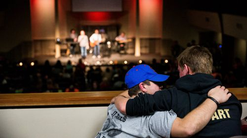 Friends comfort each other during hymns for the shooting victims. (AAP)