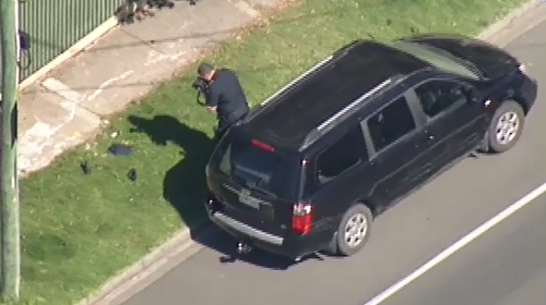 A detective takes a photo of shoes next to the black Kia Carnival, after the child was taken to hospital. (9NEWS)