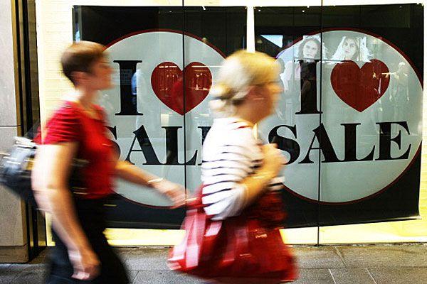 People walking past sales sign