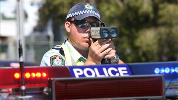 A NSW police officer zeroes his speed camera on cars