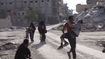 Syrian civilians run on a damaged street as they fleeing from the areas that still controlled by the Islamic State militants, in Raqqa, Syria. (Mezopotamya Agency, via AP)