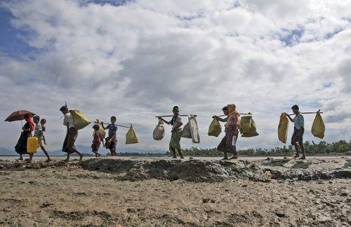 Rohingya Muslims, who crossed over from Myanmar into Bangladesh, walk towards a refugee camp in Shah Porir Dwip. (AP)