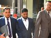 Uber driver Nazrul Islam (centre) arrives at the Downing Centre Local Courts in Sydney, Thursday, November 15, 2018.