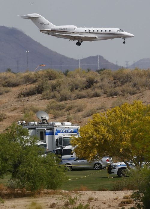 As a jet comes in for a landing at Scottsdale Airport, authorities park on a golf course near the site of the plane crash.