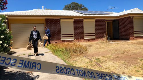 Police remove evidence from the Adelaide home this morning.
