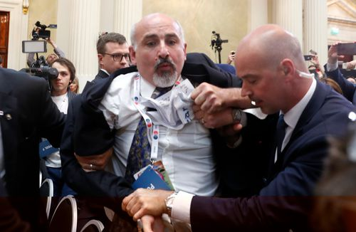 An apparent protester has been escorted out of a joint press conference between US President Donald Trump and Russian President Vladimir Putin. Image: AP