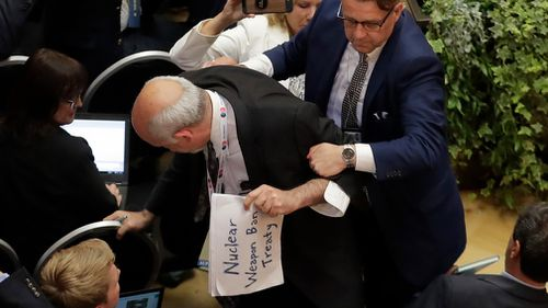 "Sam Husseini, seated with the American press corps in Helsinki, was holding a sign reading ""nuclear weapon ban treaty"". Image: AP"