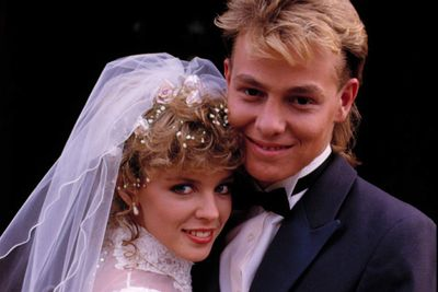 """<div align=""""left""""><B>When:</b> 1987<br/><br/>With 20 million viewers in the UK alone, not only is this wedding the highest-rating <i>Neighbours</i> episode of all time, but it set the standard up to which TV weddings (and terrible mullets) are held.</div>"""