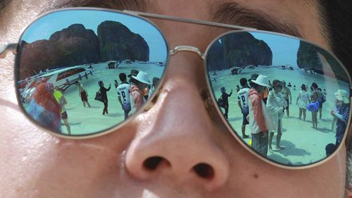 Tourists are reflected in sunglasses on Maya Bay on Phi Phi island in Krabi province, Thailand.