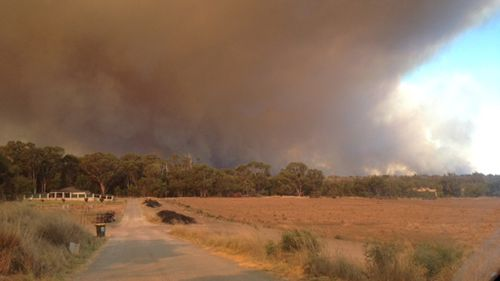 Smoke is seen rising on the horizon from Wannaroo Road. (Cassie Scoble)