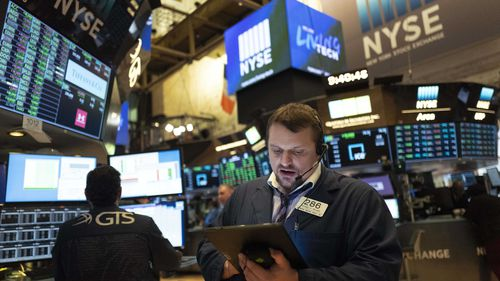 Stock trader Michael Milano works at the New York Stock Exchange, Friday, March 13, 2020.