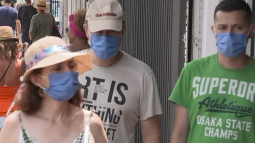 Three individuals wearing face masks in the US.