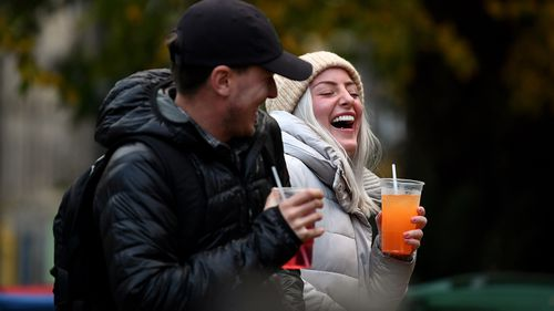 A couple drink from takeaway glasses outside a pub in the Grassmarket following last orders at 6pm on October 9, 2020 in Edinburgh, Scotland.