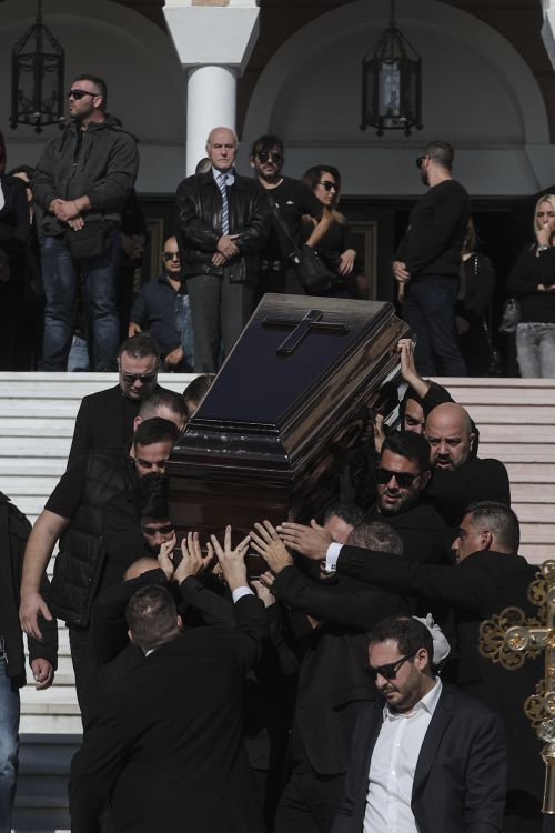 The coffin is carried down the steps of Saint Nektarios Church in Athens.