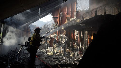 Captain Adrian Murrieta with the Los Angeles County Fire Department looks for hot spots on a wildfire-ravaged home.