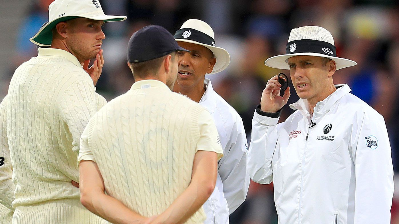 Umpires speak with players after checking the light meter during day one of the third Ashes Test match at Headingley
