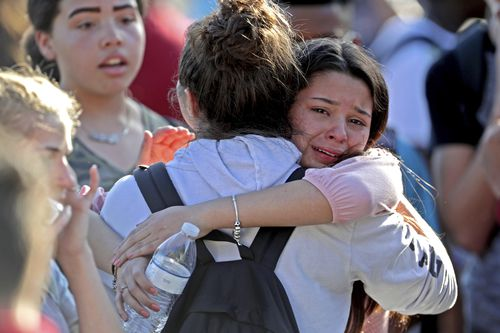 Outside the school, friends hug each other in shock and relief. Picture: AAP