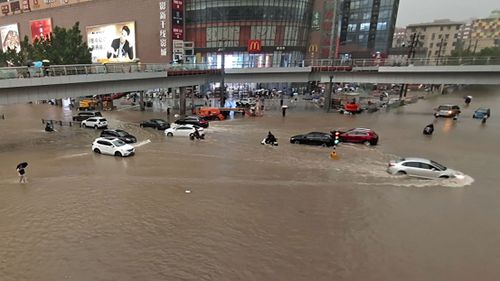 Vehicles are stranded after a heavy downpour in Zhengzhou city, central China's Henan province.