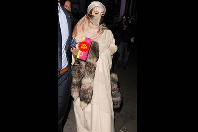 Lady Gaga descends on London Fashion Week, and as if wearing a burqa adorned with racoon tails isn't culturally insensitive enough, her purse has the bad C-word stitched onto it with sequins.