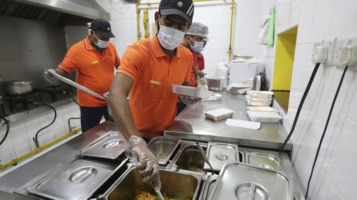 Cooks prepare free food for needy people at a restaurant in Sharjah.