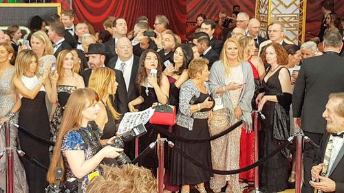 Audience members wait behind the red carpet cordon. (9NEWS/Ehsan Knopf)