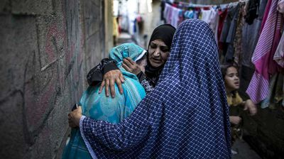 A Palestinian mother is consoled by other woman at the site of an explosion in a public playground in the beachfront Shati refugee camp in Gaza City on July 28, 2014.