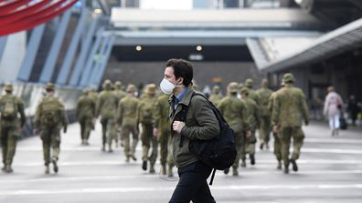 MELBOURNE, AUSTRALIA - JULY 27: A man wearing a face mask walks past as the Australian Defence Force walk through the city on July 27, 2020 in Melbourne, Australia. Victoria has recorded 532 new cases of coronavirus and six more deaths. Metropolitan Melbourne and the Mitchell shire remain in lockdown due to the rise in COVID-19 cases through community transmissions, with people permitted to leave home only for exercise, work, to buy essential items, or to access childcare and healthcare and indi