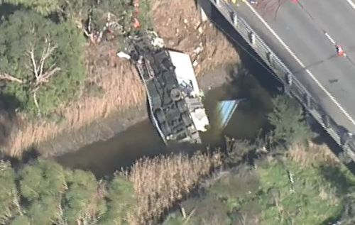 In a third incident, a young truck driver was trapped under his truck after it toppled off a bridge near Melbourne. Picture: 9NEWS.