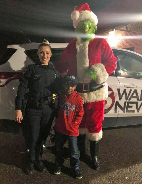 Tylon poses with Officer Develle and an actor dressed as the Grinch. (Facebook/TeDera Dwayne Graves II)